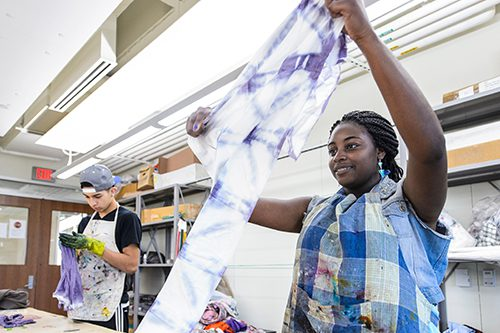 student holds up a a piece of fabric she has dyed during a Precollege Enrichment Opportunity Program for Learning Excellence
