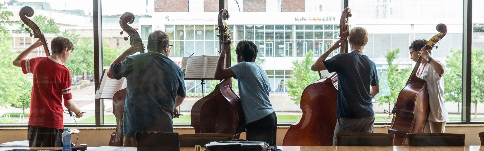 Five upright bass players practice on the UW–Madison campus during Summer Music Clinic.