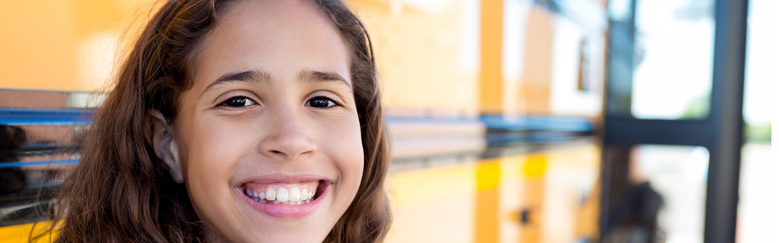 A young Latina girl smiles in front of a school bus