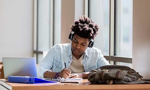 Male high school student studies in campus library