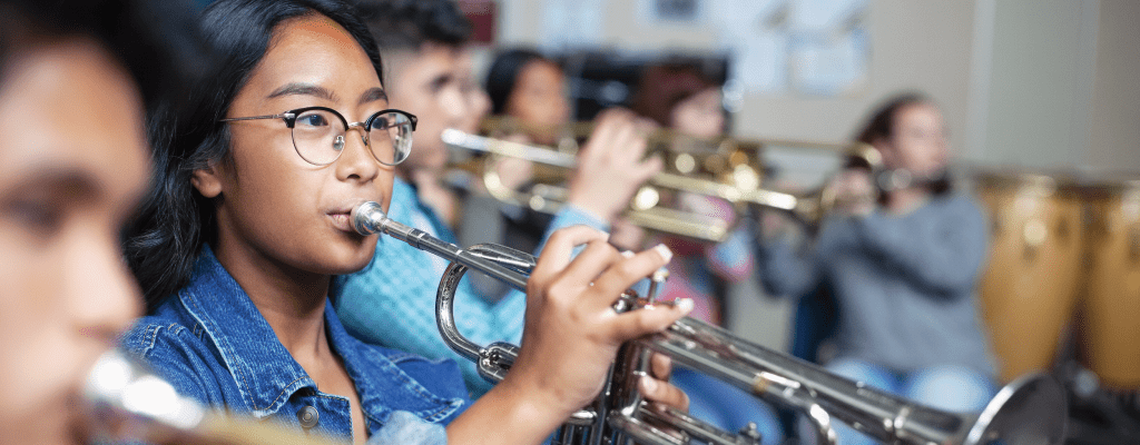 Closeup of children playing brass instruments
