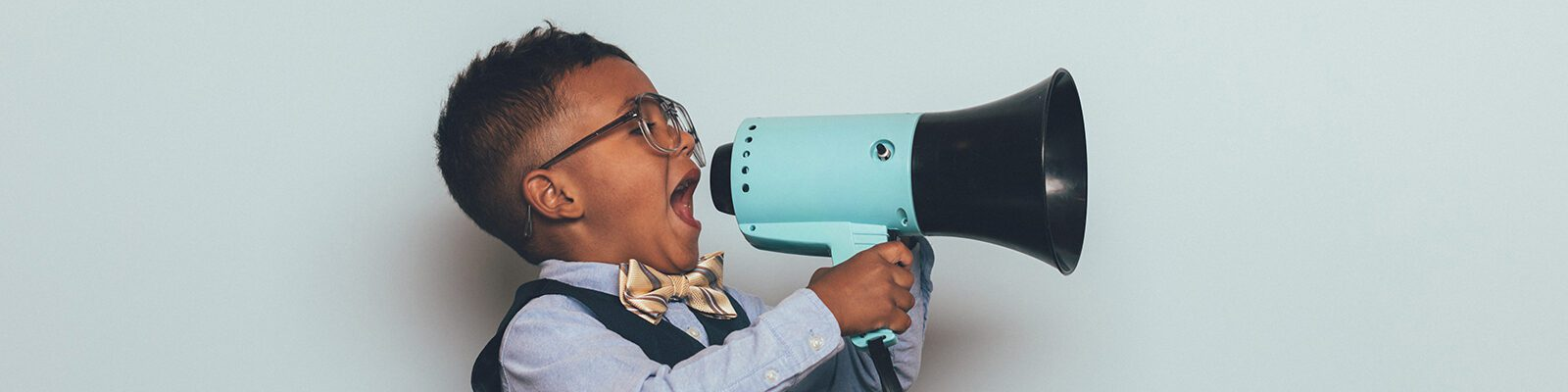 A young boy dressed in bow tie, vest and wearing eyeglasses, holds and yells through a megaphone
